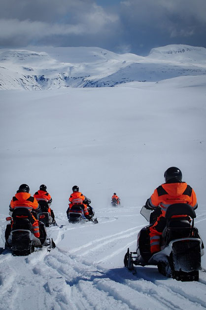 People are snowmobiling on Langjokull glacier