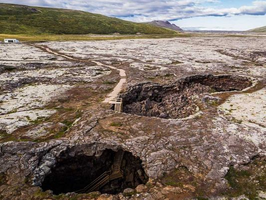The rugged lava field and the entrance of the cave